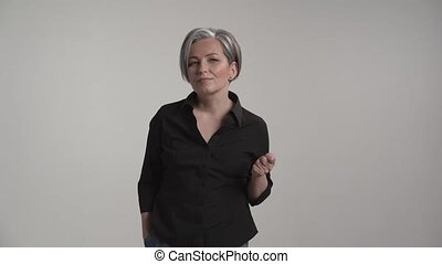 Incredulous mature woman with gray hair showing facial ...