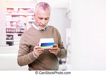 Indecisive grey-haired man reading details on a medication