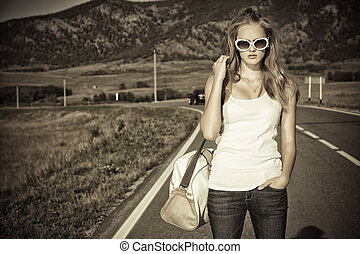 independence - Beautiful young woman posing on a road over...