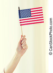 close up of woman holding american flag in hand