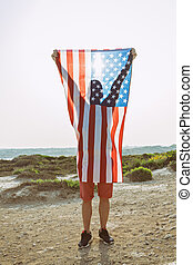 Silhouette of man holding in raised hands American Flag