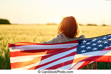 Independence day with rear view woman at field, holding American flag at sunset