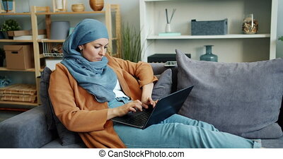 Independent Muslim girl working with laptop in apartment...