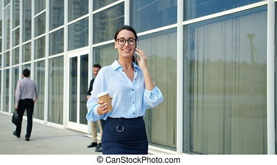 Independent woman talking on cellphone walking in city in business district smiling