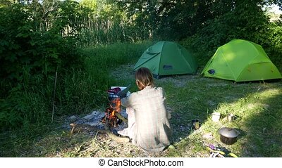 Independent young traveler woman hiker, keeping warm and relaxing by campfire
