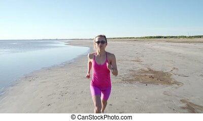 independent young woman athlete running on beach exercising...