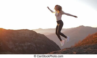independent young woman jump on top of mountain stands and enjoys the view after climbing celebrating achievement girl on edge of cliff looking at beautiful view sunset enjoying travel adventure