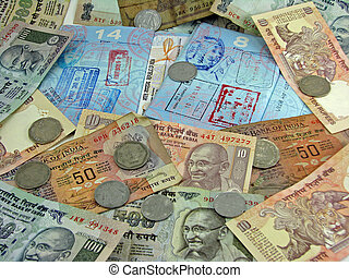India currency on top of passports with visas.