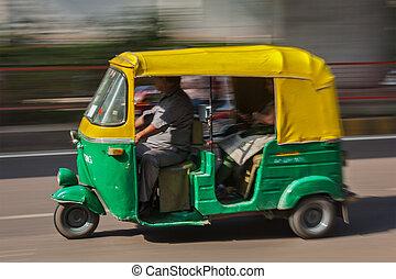 Indian auto (autorickshaw) taxi in the street. Motion blur. Delhi, India