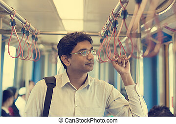 indian business male taking subway to work