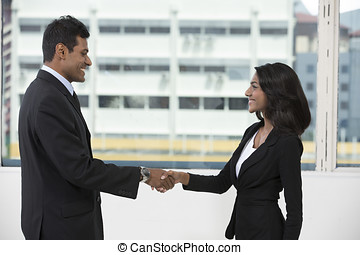 Indian business man and woman shaking hands.