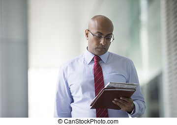 Indian Business man Outside Office reading a newspaper.