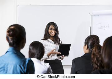 Indian Business woman giving presentation with Tablet -...
