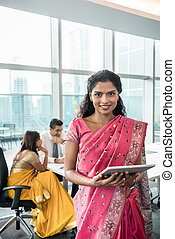 Indian business woman looking at camera while holding a tablet