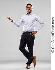 indian businessman holding something over grey