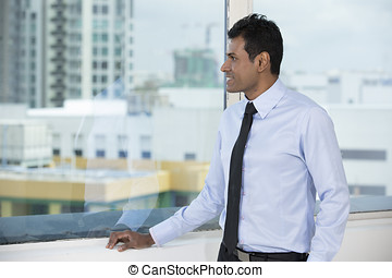 Indian businessman looking out of a window. - Thoughtful...