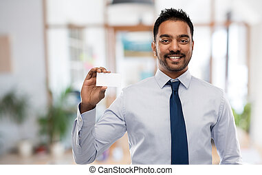 indian businessman with business card over office