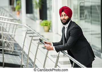 Young indian businessman in modern office with tablet.