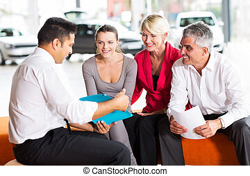indian car dealer explaining sales contract to the family...