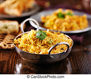 indian chicken biryana in balti dish with naan and samosa in...