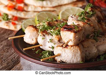 chicken tikka kebabs on skewers macro on a plate. Horizontal...