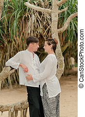 a woman with a man under a palm tree
