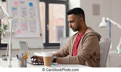 indian creative man working on laptop at office - business...