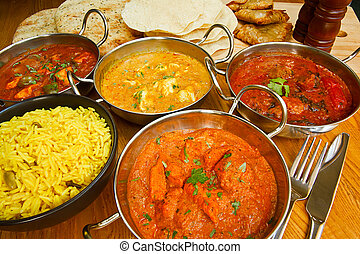 Selection of indian food with pilau rice, naan bread, poppadoms and samosas a popular choice for eating out in european countries