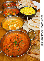 Selection of indian curries with pilau rice, naan bread, poppadoms and samosas a popular buffet choice