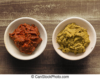 indian curry paste - close up of bowls of red and yellow...