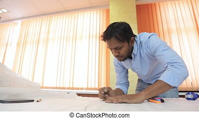 Indian engineer designer drafting draw on a table in a...