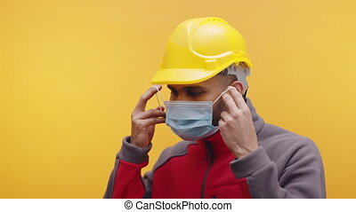 Indian engineer with yellow hard hat putting on medical mask . High quality 4k footage