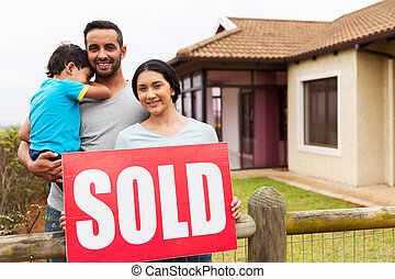 indian family holding sold sign