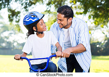 indian father helping his daughter to ride a bicycle