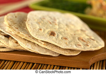 Indian flatbread called chapati on wooden board (Selective Focus, Focus on the front of the first three chapatis)