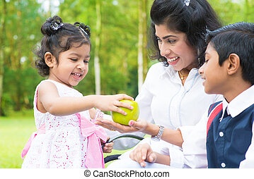 Indian girl sharing apple with family
