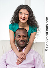 Indian girl standing over man sitting on sofa and hugging. black african man sitting on sofa and smiling