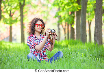 Indian girl with camera in the park.