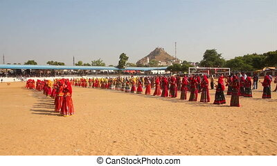 Indian girls in colorful ethnic attire dancing at Pushkar camel fair India