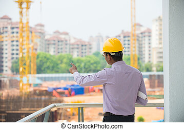 indian male architect inspecting site with construction background