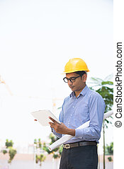 indian male architect inspecting site with construction backgrou