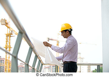 indian male architect reading plans with construction background