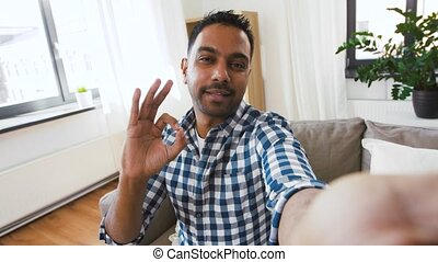 indian male blogger recording video blog at home - blogging,...