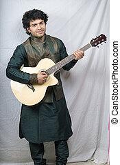 indian male model in green kurta holding guitar smiling