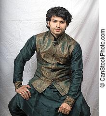indian male model in traditional green kurta sitting pose