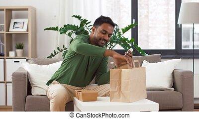 indian man checking takeaway food order at home -...