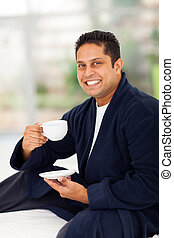 indian man drinking coffee on bed