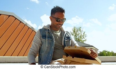 indian man eating pizza and drinking beer outdoors - leisure...