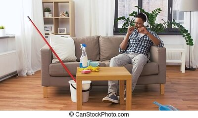 indian man in headphones after cleaning home - people,...