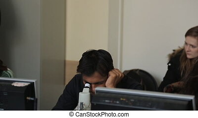 Indian man looks through a microscope in classroom for...